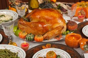 A delicious Thanksgiving dinner is displayed proudly on a dining room table.