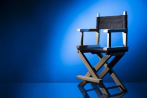 A directors chair surrounded by light waits for the action to start.