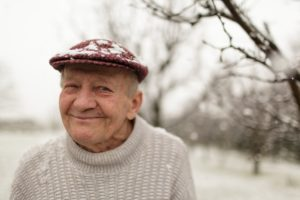 An older man with a snow-covered cap smiles outdoors.
