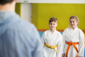 A brother and sister wait patiently for their martial arts class to start.