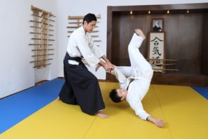 A martial arts master flips his opponents onto the mats.