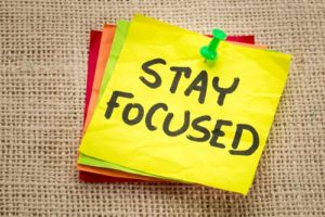 "A stack of Post-It notes displays ""Stay Focused"" on the top of the stack."