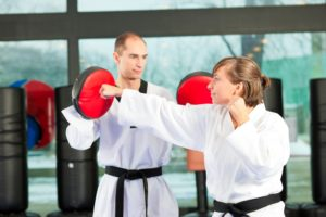 A martial arts instructor holds practice paddles for a fellow black belt to strike a punch.