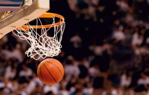 A basketball swishes through a net in front of a crowd of spectators.