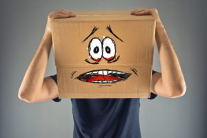 A man clutches a cardboard box displaying a nervous face over his head.