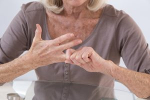An elderly woman rubs her hands in pain from arthritis in her fingers.