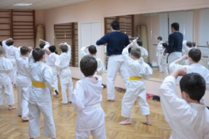 A room full of young martial arts students run drills during class.