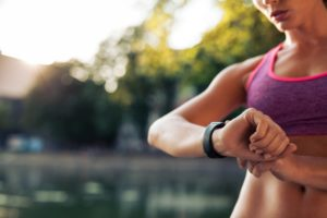 A woman checks her stopwatch while outside for run.