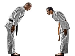 A young martial artist bows to his instructor as a sign of respect.