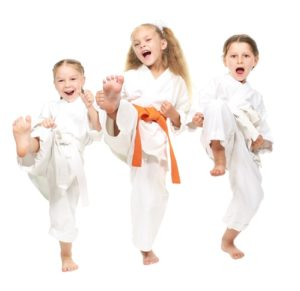 Three young martial artists practice their kicks during training.
