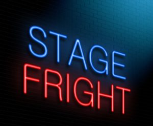 "A neon sign reading ""Stage Fright"" beams brightly on a brick wall."