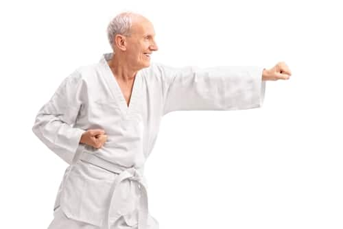 An elderly man smiles joyfully as he begins his martial arts training.
