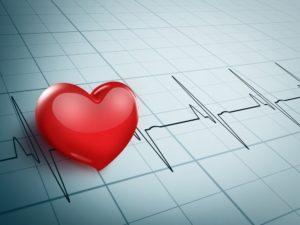 A big heart sits on an EKG chart.