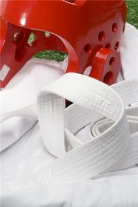 A red sparring helmet rests on a clean white martial arts uniform.