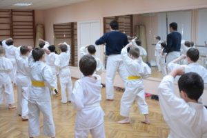 Young martial artists train hard and have fun in a full studio.