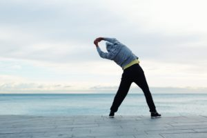 An adult takes time to stretch in front of the ocean before continuing his workout.