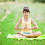 A young girl sits calmly on a blanket in the grass as she meditates with closed eyes and pressed palms.