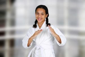 A young white belt smiles while holding a martial arts stance.