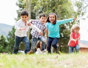 An energetic group of young children play excitedly outside.