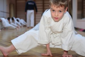 Young martial artist concentrates as he stretches in class.