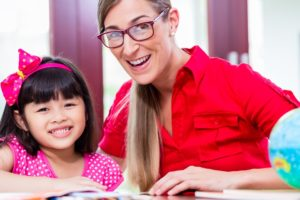 Young student smiles with her instructor.