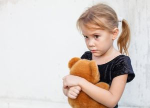 Nervous young girl hugs a stuffed animal.