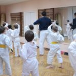 A class of young martial artists follow their instructor's lead at the front of the class.