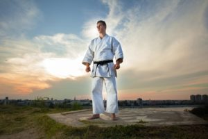 Man in martial arts uniform ready to train outside.