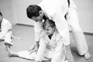 A black and white photo of a student training with a martial arts instructor