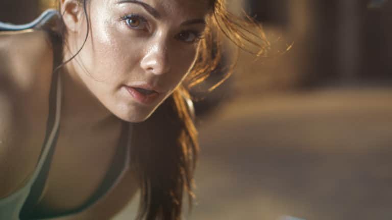 Close-up Shot of a Beautiful Athletic Woman with Anxiety Looks into Camera. She's Tired after Intensive Cross Fitness Exercise.