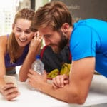 Couple Wearing Gym Clothing Reading Message On Mobile Phone about marketing your gym