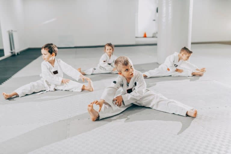 young martial arts students stretching before class